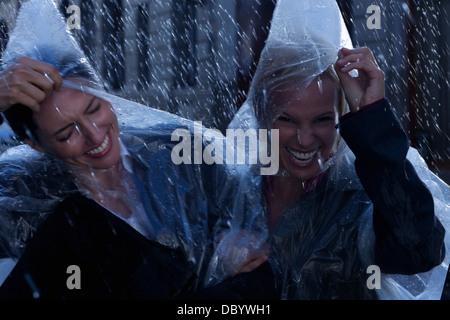 Laughing businesswomen wearing ponchos in rain - Stock Photo