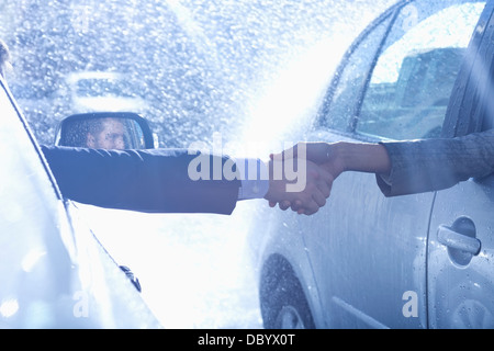 Businessman and businesswoman extending handshake from cars in rain - Stock Photo