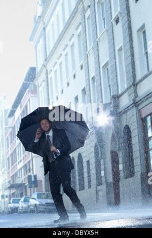 Businessman talking on cell phone under umbrella in rainy street - Stock Photo