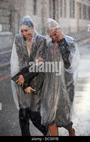 Businesswomen in ponchos walking in rainy street - Stock Photo