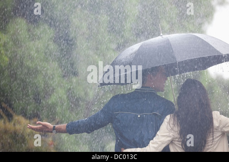 Couple walking with arms outstretched under umbrella in rain - Stock Photo