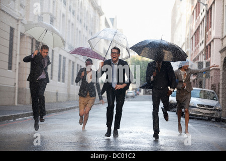 Business people with umbrellas running in rainy street - Stock Photo