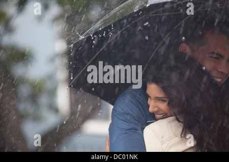 Happy couple hugging under umbrella in rain - Stock Photo
