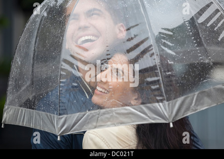 Happy couple under umbrella looking up at rain - Stock Photo