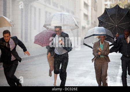 Enthusiastic business people with umbrellas running in rainy street - Stock Photo