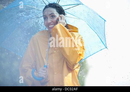 Happy woman talking on cell phone under umbrella in rain