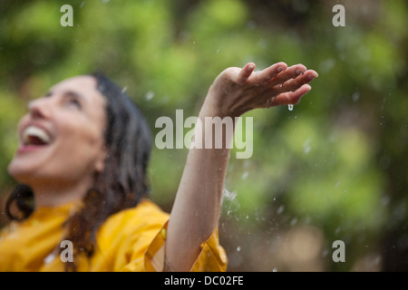 Enthusiastic woman standing with arms outstretched and head back in rain - Stock Photo