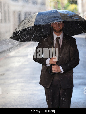Happy businessman with umbrella walking in rainy street - Stock Photo