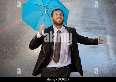Enthusiastic businessman with tiny umbrella in rainy street - Stock Photo