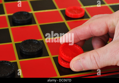 Playing draughts / checkers game on a checker board - Stock Photo