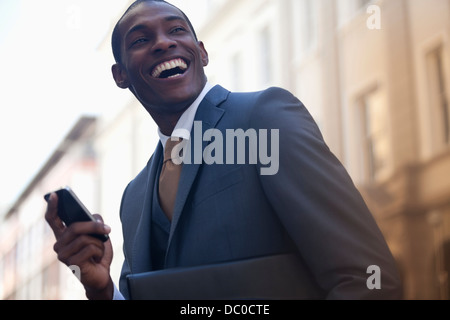 Enthusiastic businessman text messaging with cell phone - Stock Photo