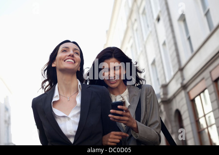 Happy businesswomen text messaging with cell phone - Stock Photo
