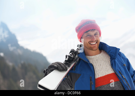 Portrait of smiling man holding skis - Stock Photo