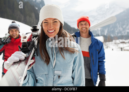 Portrait of smiling friends carrying skis - Stock Photo