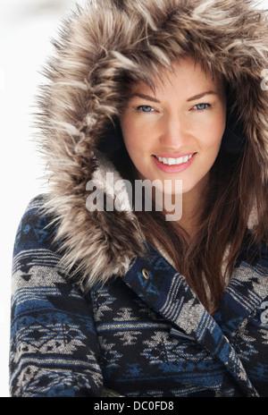 Portrait of smiling woman wearing fur hood - Stock Photo