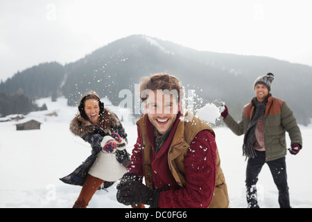 Portrait of playful friends throwing snowballs in field - Stock Photo