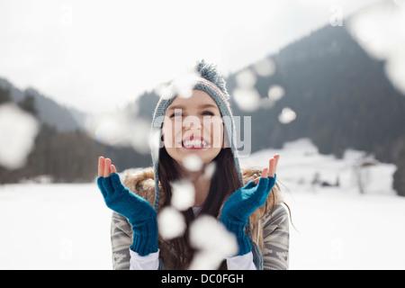 Happy woman enjoying falling snow in field - Stock Photo
