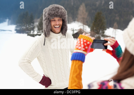 Woman photographing man in fur hat in snowy field - Stock Photo
