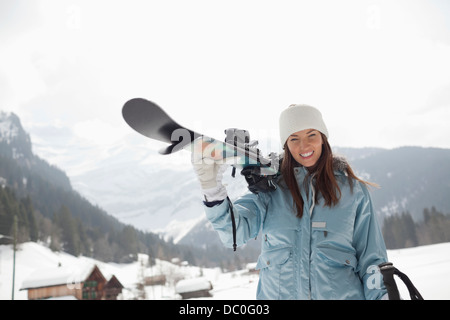 Portrait of enthusiastic woman carrying skis in snowy field - Stock Photo