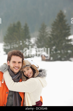 Portrait of smiling couple hugging in snowy field - Stock Photo