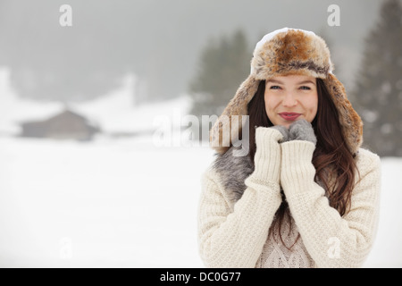 Portrait of smiling woman wearing fur hat and gloves in snowy field - Stock Photo