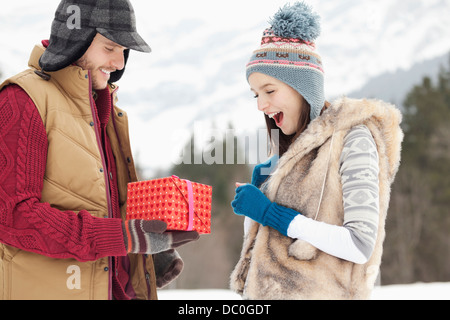 Man surprising woman with gift in snowy field - Stock Photo