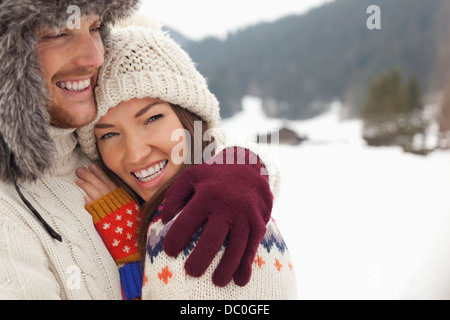 Close up portrait of happy couple hugging in snowy field - Stock Photo