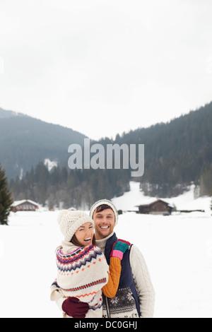 Portrait of happy couple hugging in snowy field - Stock Photo