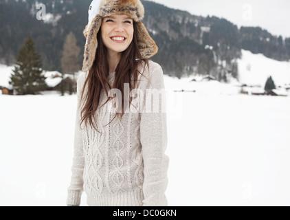 Happy woman wearing fur hat in snowy field - Stock Photo