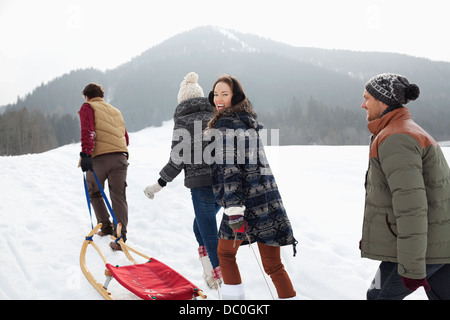 Happy friends pulling sleds in snowy field - Stock Photo