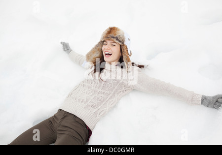 Enthusiastic woman making snow angel - Stock Photo