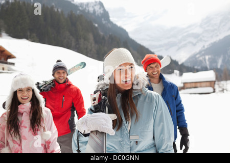 Happy friends carrying skis in snowy field - Stock Photo