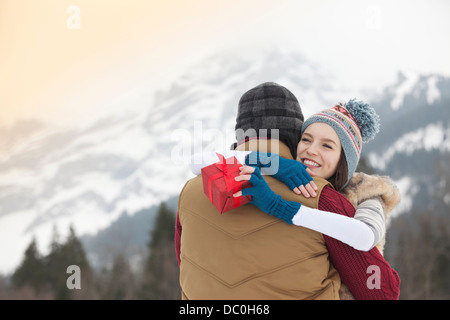 Happy woman holding gift and hugging man with mountains in background - Stock Photo