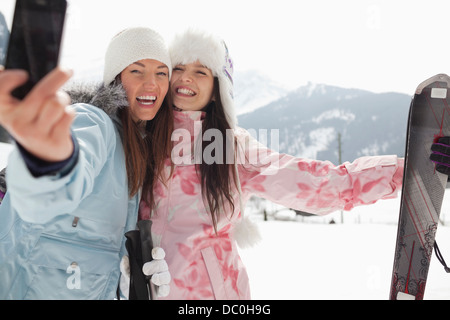 Enthusiastic women with skis taking self-portrait with camera phone in field - Stock Photo