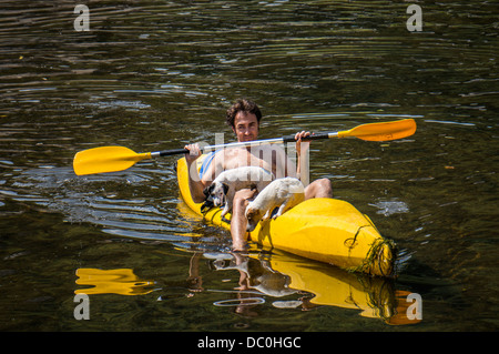 Man and dogs in a hire canoe on the river Dronne in the commune of Brantôme, in the Dordogne department in south - Stock Photo