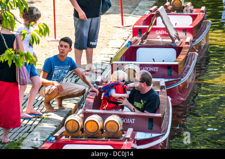 Father and young son boarding a boat for a tourist ride on the river Dronne, on a hot summer day in Brantôme, Dordogne - Stock Photo