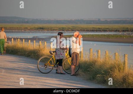 Middle aged couple taking a photo in the early evening sunshine in the coastal town of Le Crotoy, the Somme department - Stock Photo