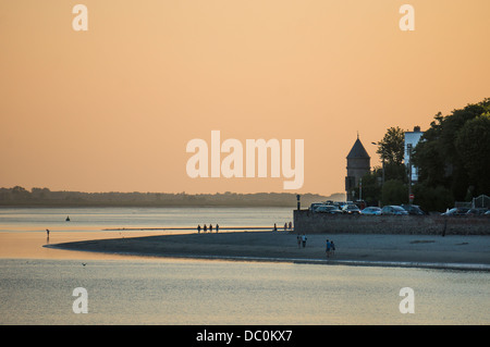 Groups of people walking on the beach at dusk in the bay of the coastal town of Le Crotoy in the Somme department - Stock Photo