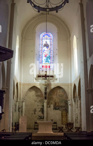 Stained glass window and cross in the tall and narrow Church of Saint-Nicolas in Trémolat, Dordogne, Nouvelle-Aquitaine - Stock Photo