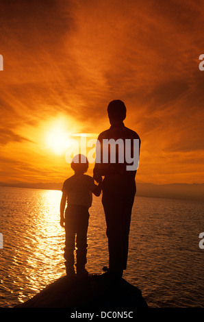 1990s SILHOUETTED FATHER AND SON WATCHING SUNSET OVER WATER - Stock Photo
