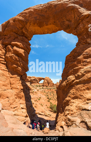Walkers resting under Turret Arch with South Window arch in the distance, The Windows Section, Arches National Park, Utah, USA