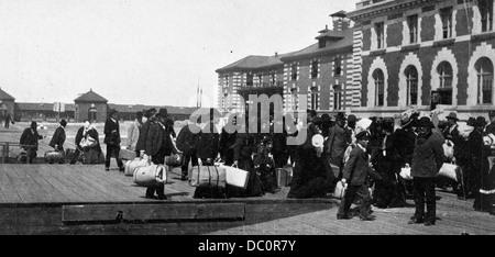 1900s 1910s 1920s ANONYMOUS IMMIGRANTS TO AMERICA LANDING ON ELLIS ISLAND NEW YORK USA - Stock Photo