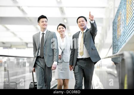 Business team walking on moving walkway - Stock Photo