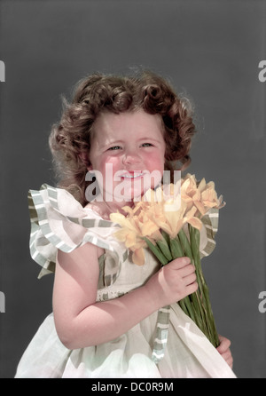 1940s 1950s PORTRAIT SMILING BRUNETTE GIRL HOLDING BOUQUET OF YELLOW JONQUILS LOOKING AT CAMERA - Stock Photo