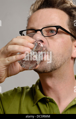 A man drinks a glass of water - Stock Photo