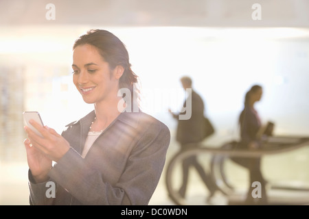 Smiling businesswoman text messaging with cell phone - Stock Photo