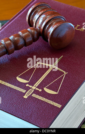 Law concept  Family Law book with scales of justice and double edged sword motif with Judges wooden gavel - Stock Photo