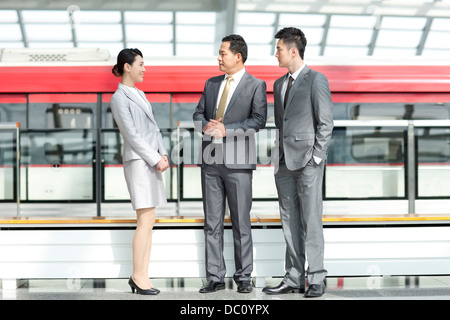Business persons talking at subway station - Stock Photo