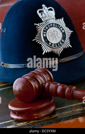 Legal concept Metropolitan Police helmet with judges gavel in London law courts situation UK - Stock Photo