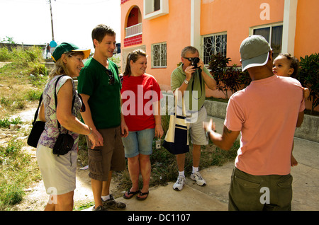 Tourist father photographs Cuban father and baby, as tourist mother, son and daughter watch. - Stock Photo